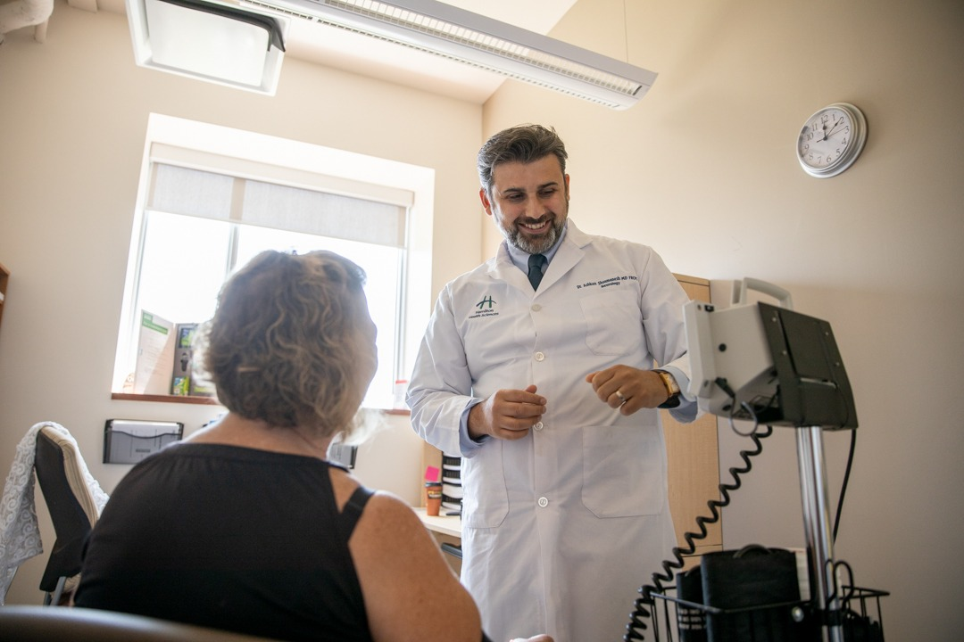 A research scientist cares for a patient in his office.
