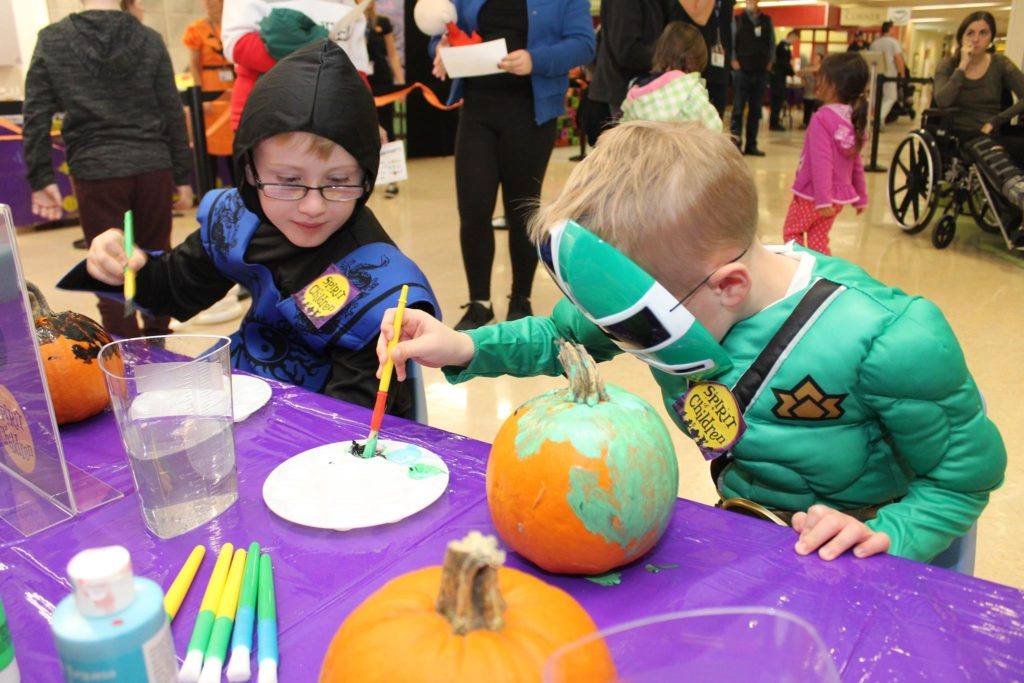 Two children doing crafts in costume
