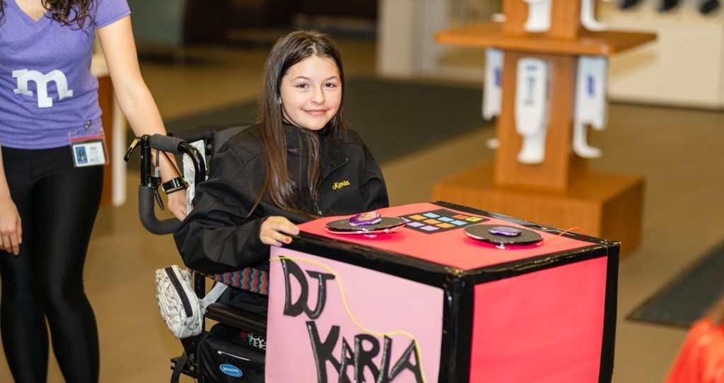 girl in wheelchair with DJ table on her lap