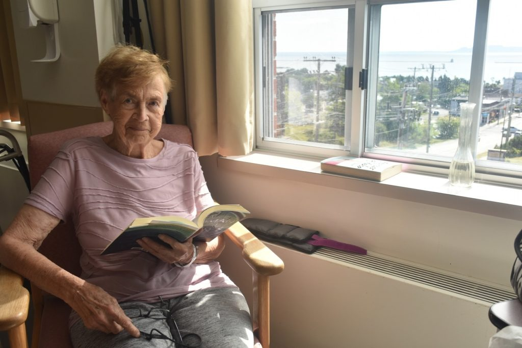 Verna Ross reads a book in her hospital room.