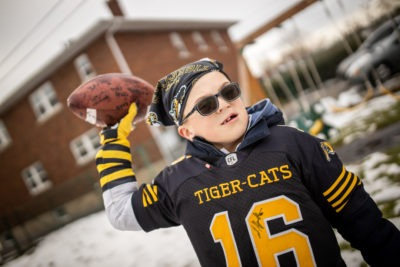 Carter Dery wearing a Ticats jersey and preparing to throw a football