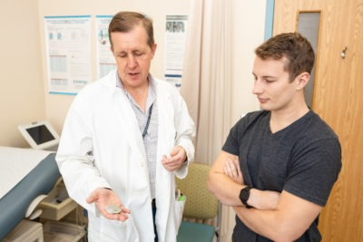 Dr. Jeff Healey shows pacemaker to Jason Baum