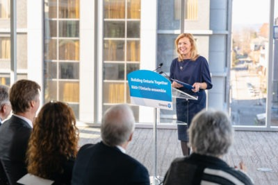 Deputy Premier and Minister of Health, the Honourable Christine Elliott stands at a podium making an announcement