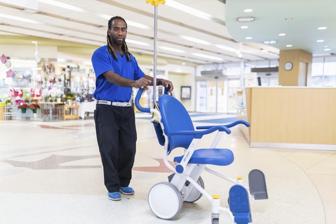 Porter, Alleyne Francis, pushes a wheelchair