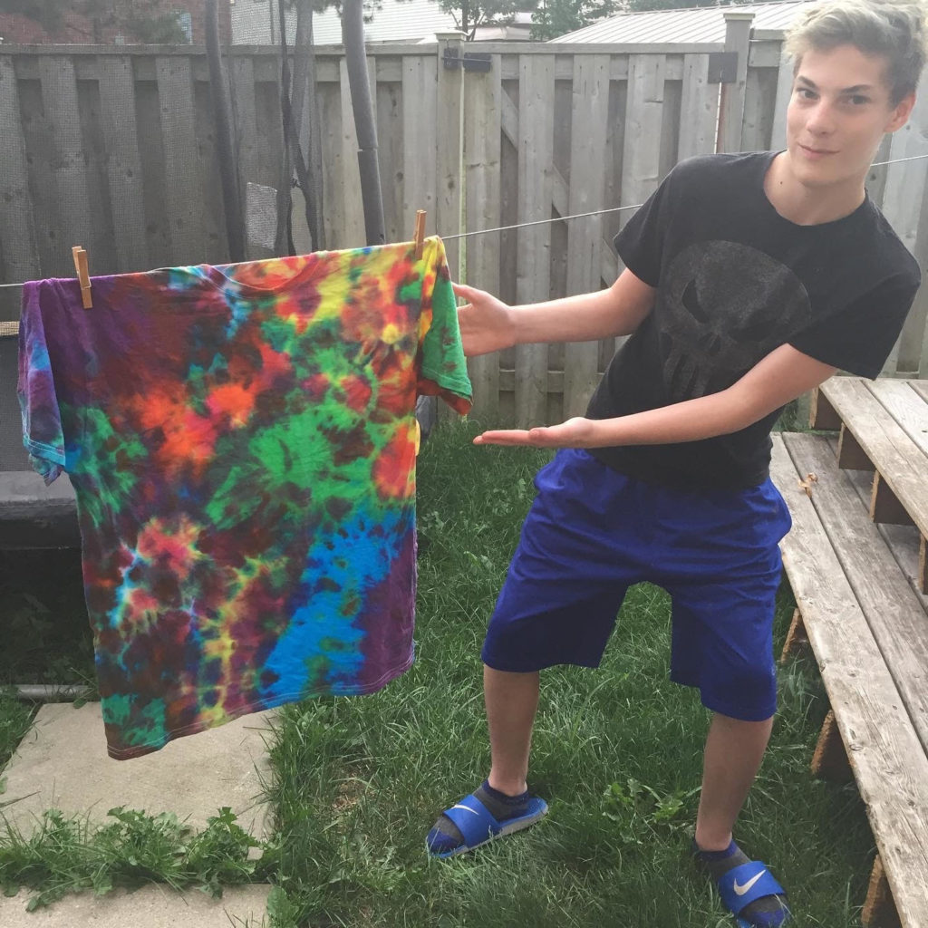 Ciaran holding up a tye-dye shirt