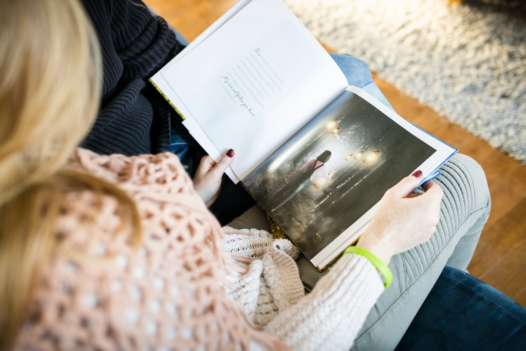 woman holding open a book with a large picture