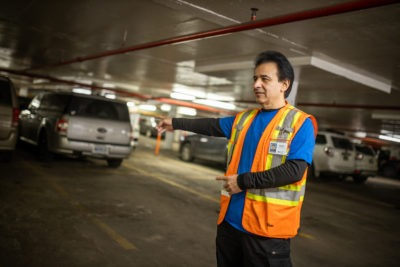 A parking lot attendant directs cars in an underground garage.