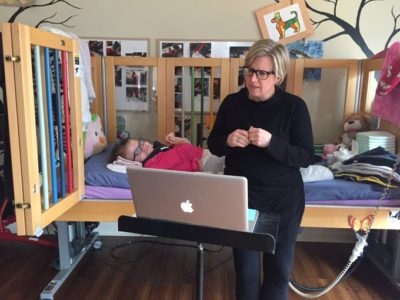 A woman sits on the edge of her daughter's bed, speaking to a laptop computer. The girl in the bed wears glasses. The bed has railings to prevent falls.