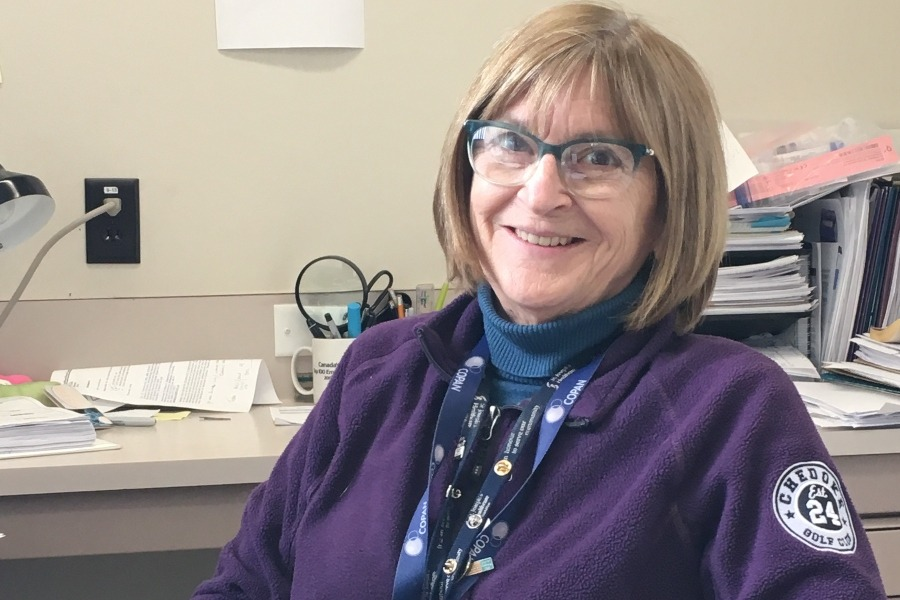 Candy Rutherford sits at her desk in the regional lab, wearing a purple sweater