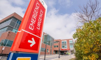 A outdoor sign pillar directing to the emergency department at Juravinski Hospital