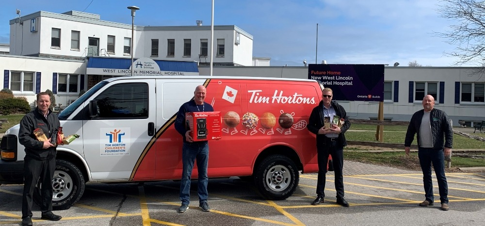 Four people stand in front of a Tim Hortons van, parked outside of West Lincoln Memorial Hospital