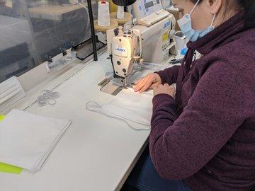 woman sews a mask at Niko Apparel