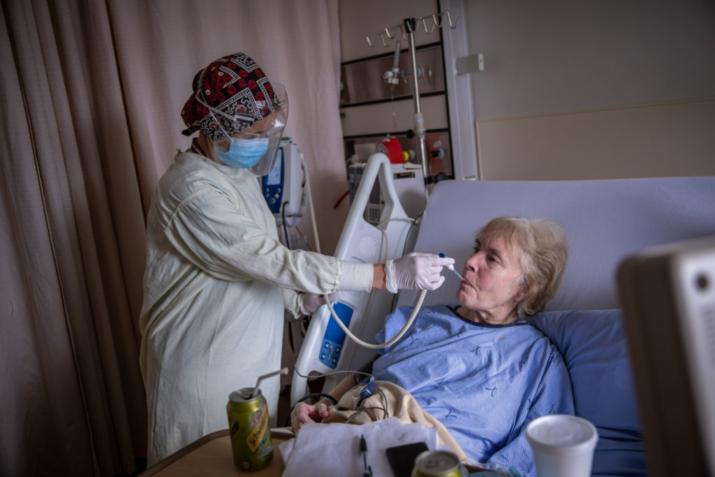 A health care provider in full personal protective equipment takes the temperature of a COVID patient at Hamilton General Hospital