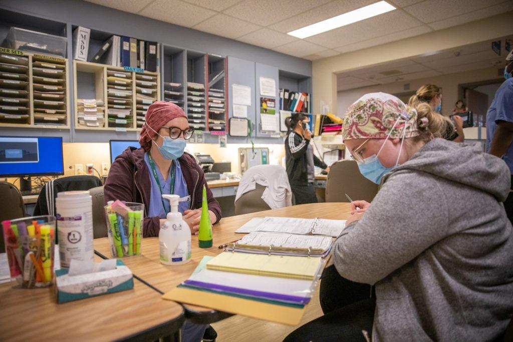 Two nurses do paperwork at their nurses station.
