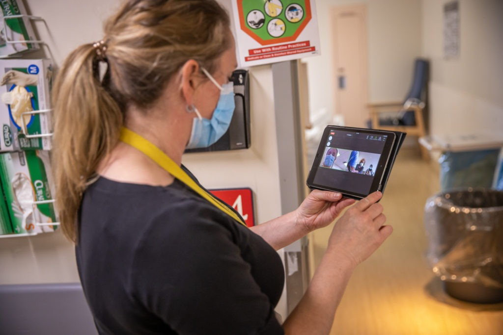 Staff help set up a digital family visit on a laptop.