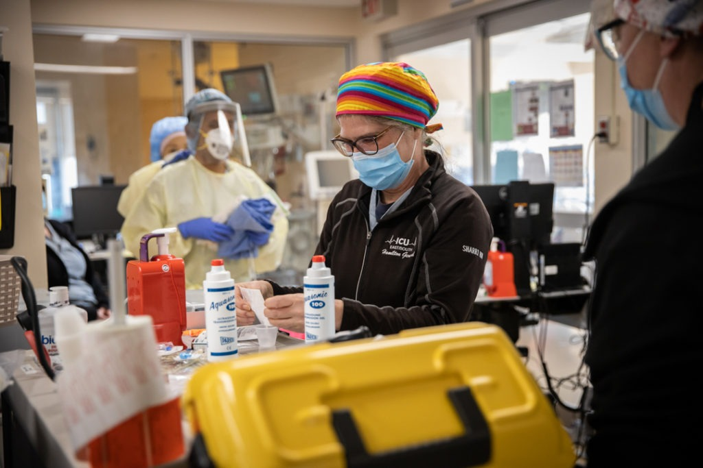 A nurse prepares supplied for staff that are inside a patient room.