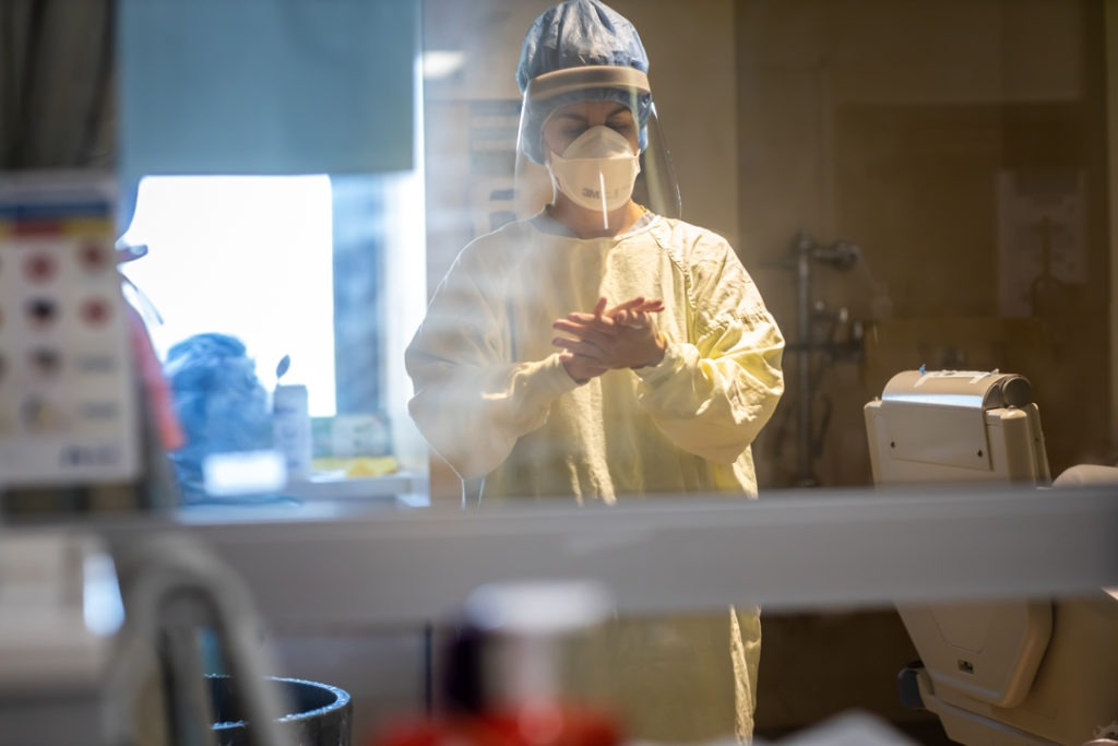 An ICU staff member washes their hands before leaving the room.