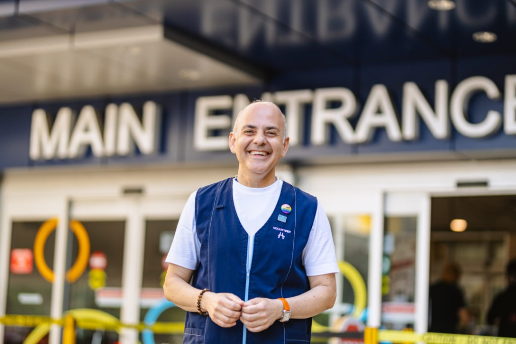 Man, smiling, standing in front of Main Entrance at McMaster University Medical Centre