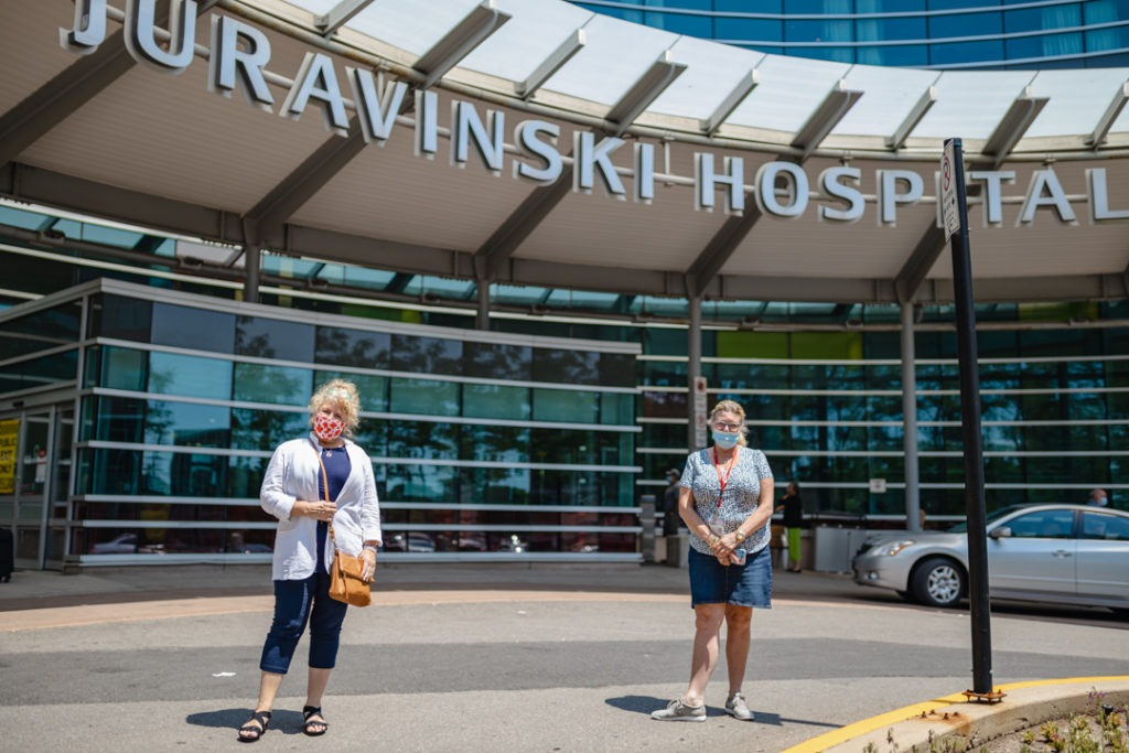 Family caregiver Jeanette Arsenault and social worker Victoria Gibbins stand outside the Juravinski Hospital main entrance. The hospital sign is visible above their heads.