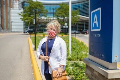 Jeanette Arsenault stands on the driveway at the Juravinski Hospital. She wears acloth facemask covered in red maple leaves.