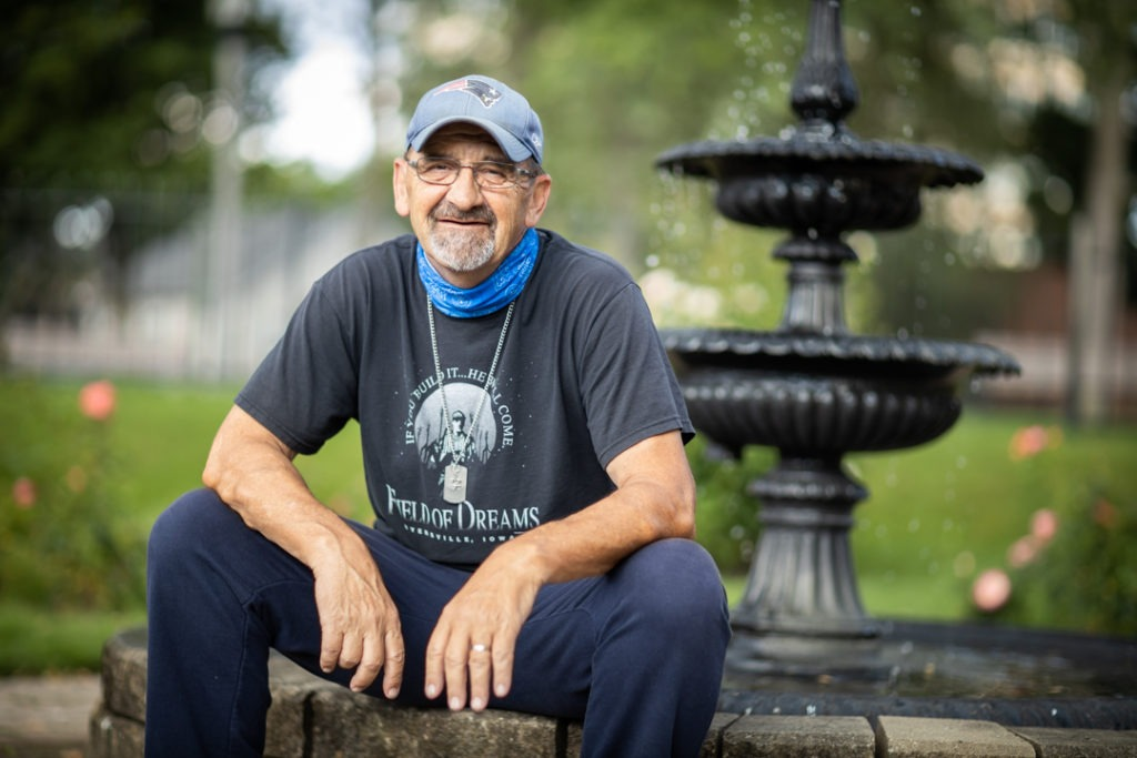 A man wearing a ball cap sits in a park by a fountain