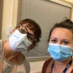 Two female hospital workers wearing disposable masks