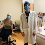 Hospital workers pose for the camera, wearing personal protective equipment
