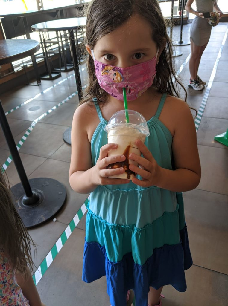Young girl holding a drink, wearing a face mask