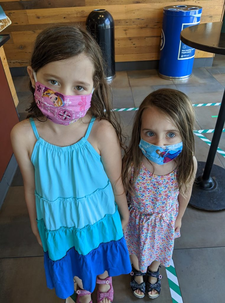 Two young girls wearing cloth masks