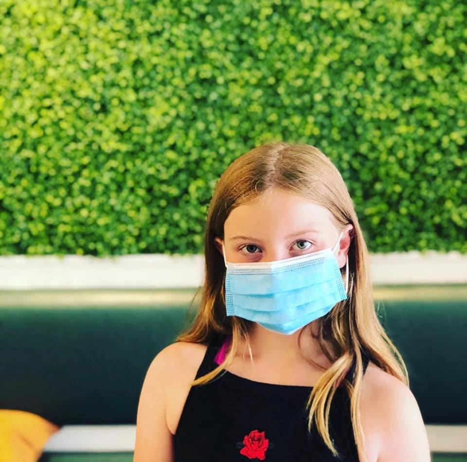 Young girl wearing disposable mask