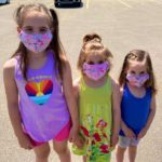 Three young girls wearing cloth masks