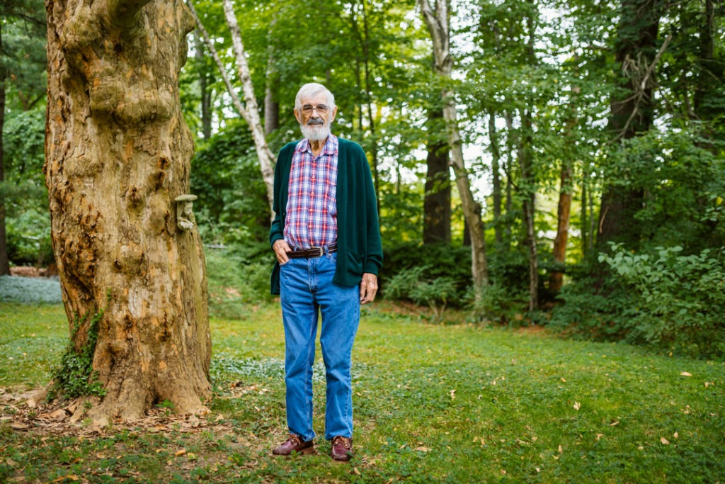 An 80-year-old man who is a Hamilton Health Sciences patient stands beside a mature tree