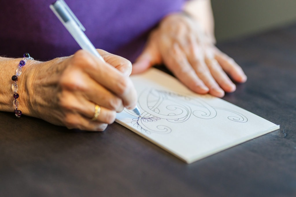 A person's hand is drawing intricate line drawings on a piece of paper