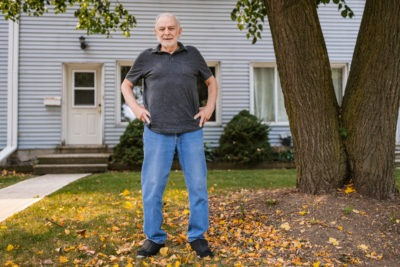 Peter Gillie stands in front of a house