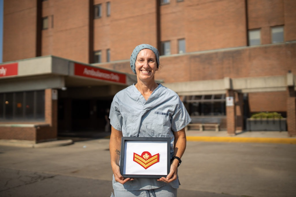 Nurse dressed in hospital scrubs, holding badge that represents her military promotion