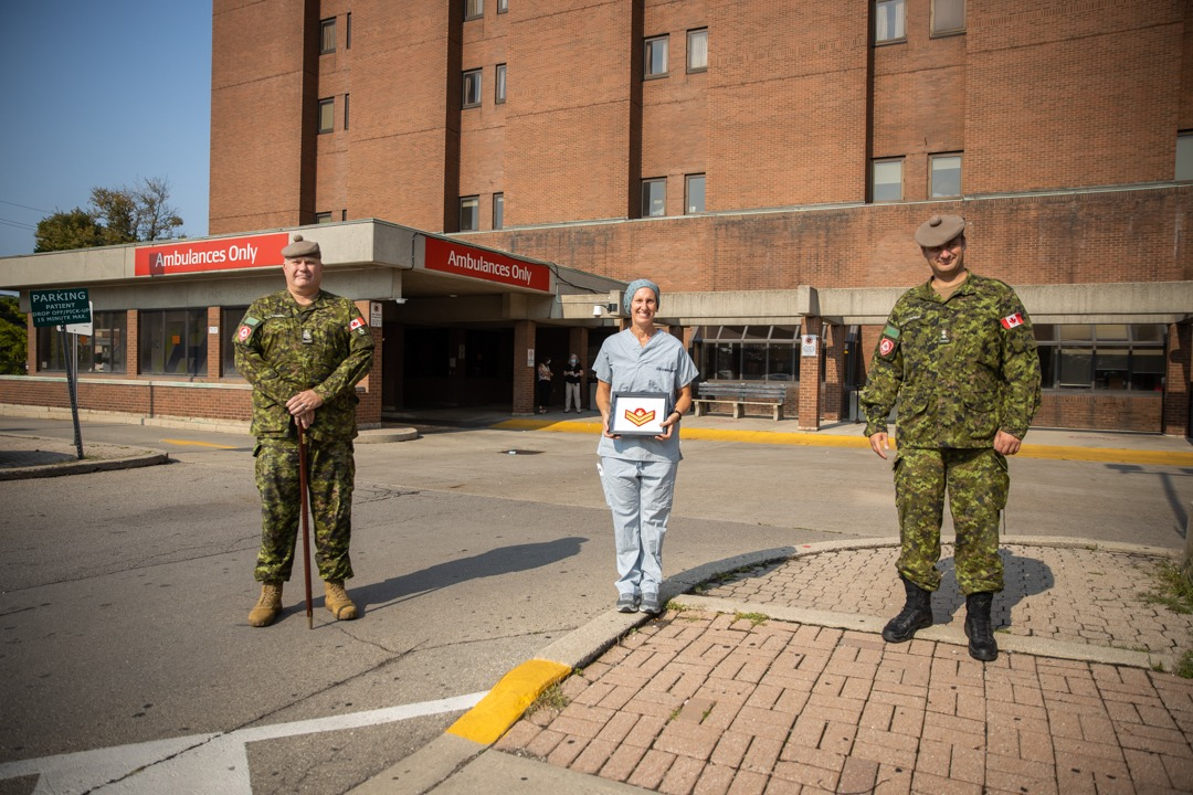 Two military members stand on either side of nurse outside hospital