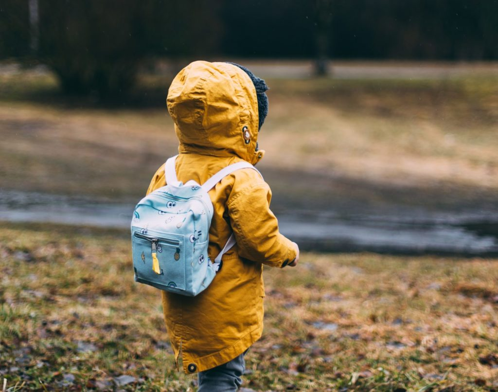 Image of a child facing away in a yellow jacket