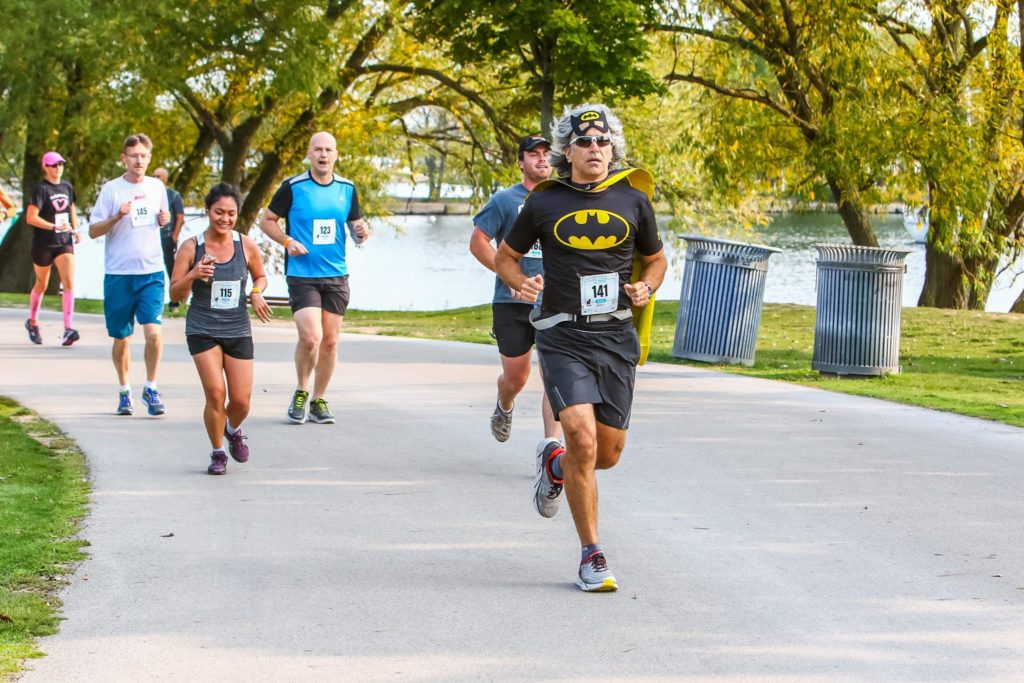 Peter running in a Batman costume. There are other runners behind him.