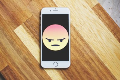 Phone with angry emoji on its screen