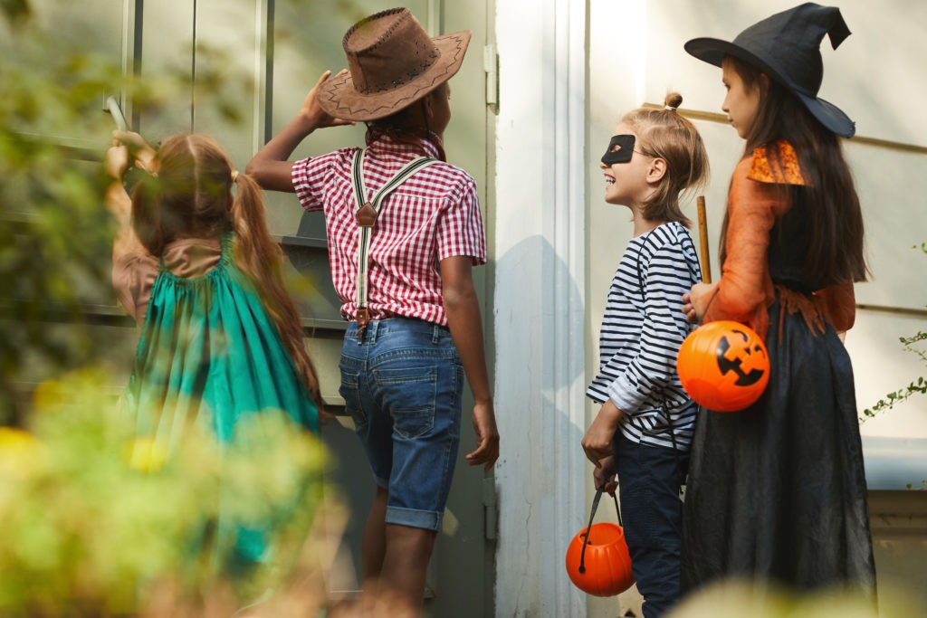 Four children in Halloween costumes knocking on the door and saying, trick or treat