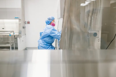 A pharmacy technician works at a lab compounding area wearing a full facemask and shield