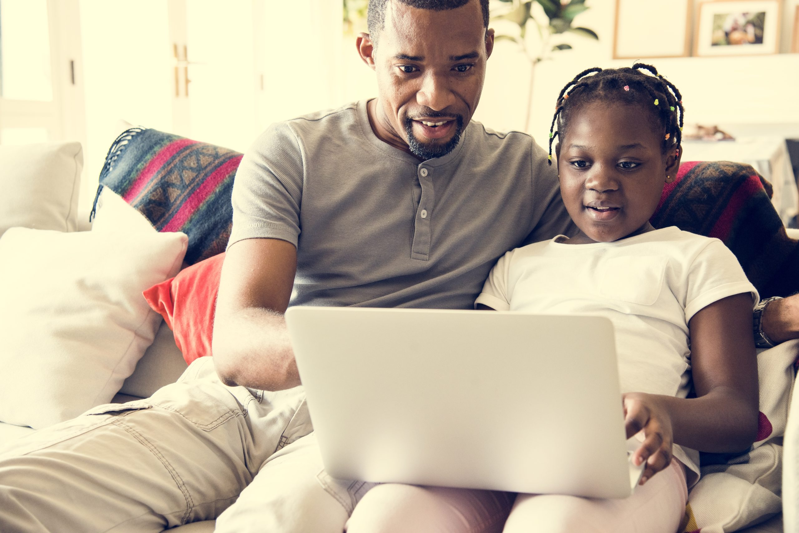 Father and daughter on the couch, looking at laptop