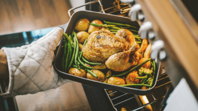 Person removes roasted poultry and veggies from oven