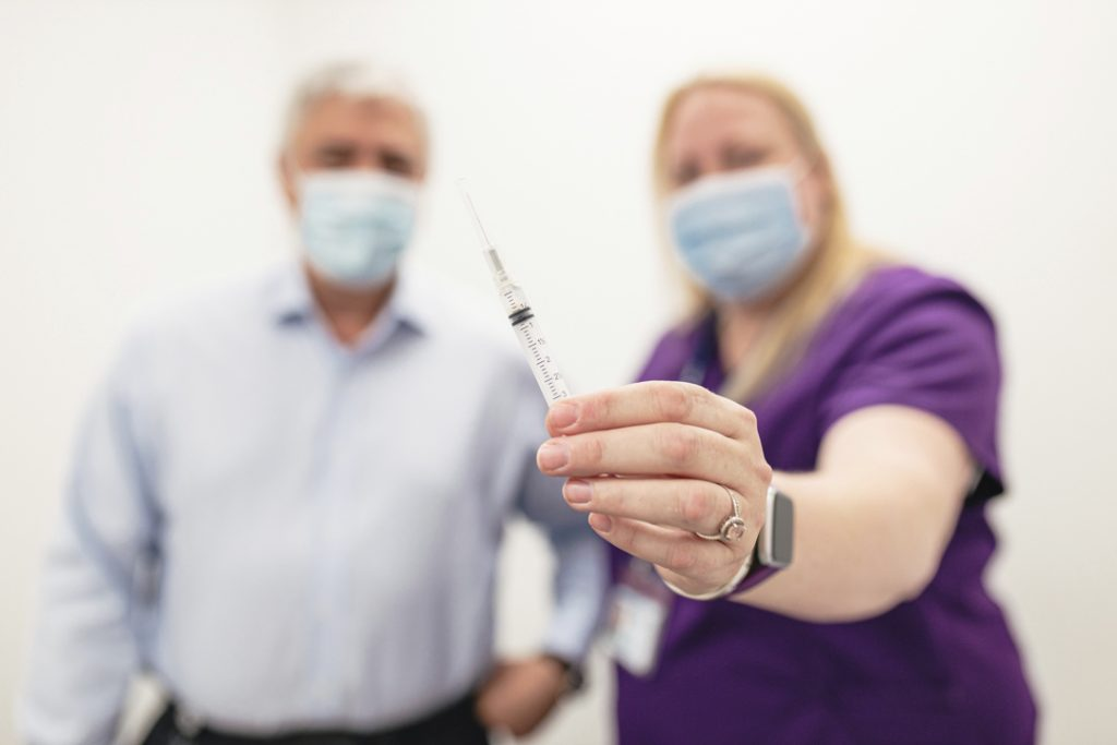Rob MacIsaac and Employee Health Services nurse out of focus, holding the flu vaccine up close