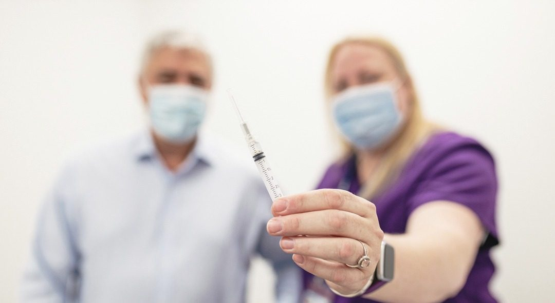 Two blurry people wearing masks in the background, flu shot needle up close