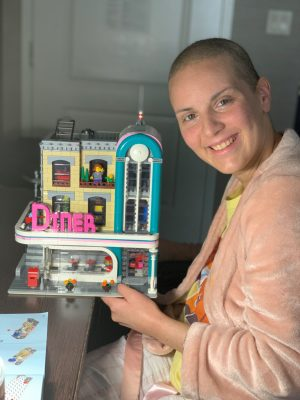 Heather Allen poses in her hotel with a LEGO structure she built during her time in isolation.