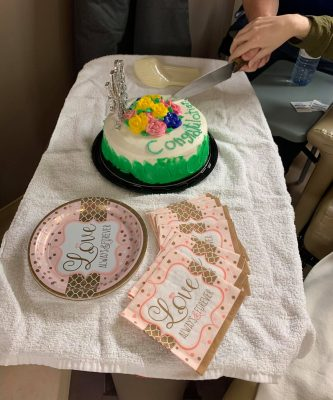 "Icing spells ""congratulations"" on a wedding cake being cut by two people. The cake sits on a hospital table covered in a white towel. Paper plates and napkins alongside the cake say ""love"" on them."