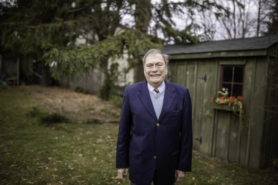 Ted Aylan-Parker stands in a wooded yard