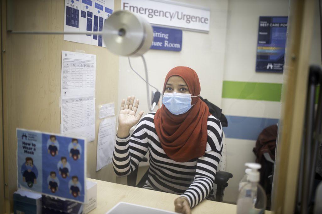 Anum Fatima sits behind a plexiglass barrier at Hamilton General Hospital