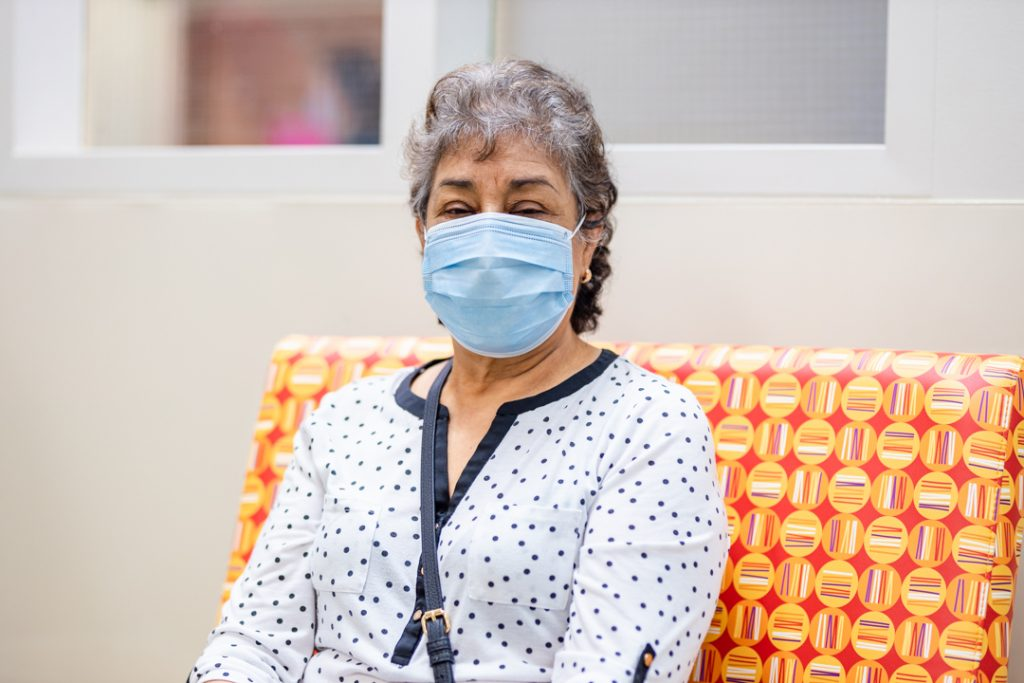 A woman wears a medical mask and sits in a hospital waiting room on a brightly-coloured chair